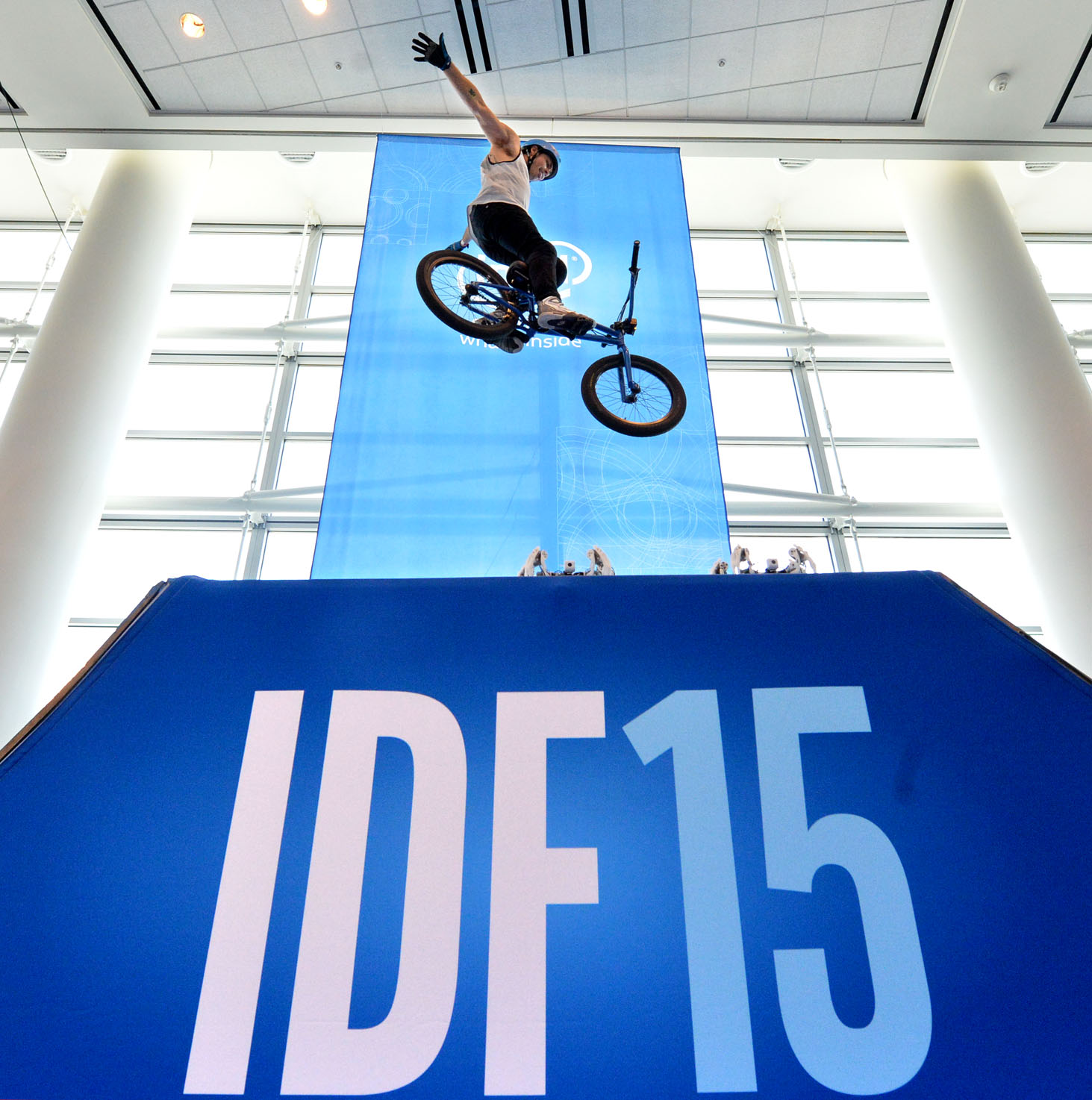 """A BMX rider performs a trick with a bicycle with an Intel Curie moduleÊattached during the Intel IDF 2015 held at the Moscone Center in San Francisco, Calif., on Tuesday, August 18, 2015. The Curie module packs a robust set of features into its tiny size that are ideal for """"always-on"""" applications such as social media, sports, and fitness activities."""